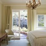 Dormitor mobilat clasic cu candelabru inflorat draperii romane la ferestre si draperii asortate la usa
