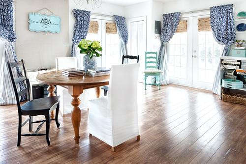 Living cu pardoseala din lemn mobilat in stil rustic si draperii albastre