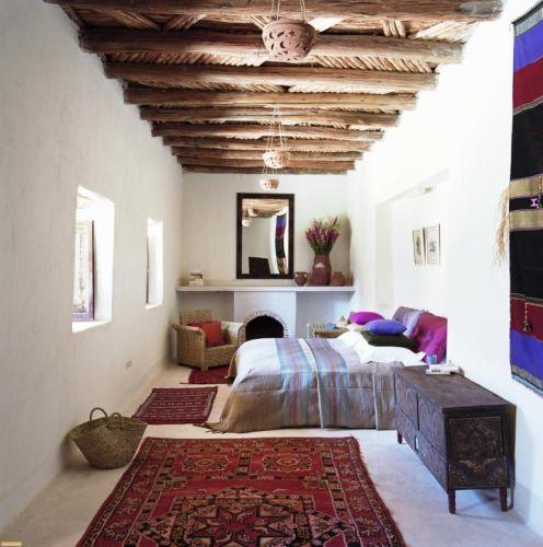 Dormitor simplu amenajat in stil marocan cu grinzi de lemn pe tavan