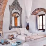 Oglinda din lemn cioplit cu motive marocane asezata deasupra patului