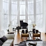 Perete curbat din sticla, pian negru si canapea alba