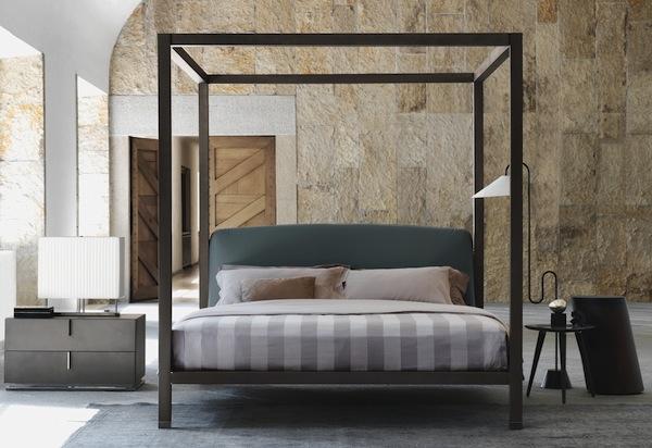 Dormitor mediteranean cu pereti cu piatra si pat cu baldachin
