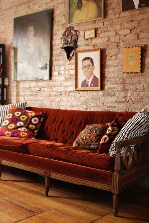 Canapea de catifea si perete cu caramida