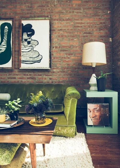 Canapea verde din catifea in living cu pereti din caramida